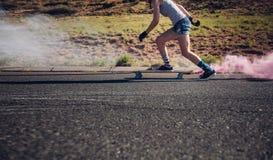 Mujer joven longboarding abajo del camino Fotos de archivo