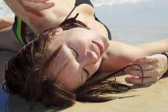 Mujer joven lounging en la playa Fotos de archivo