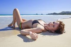 Mujer joven lounging en la playa Foto de archivo libre de regalías