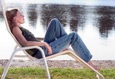 Mujer joven lounging en una silla de cubierta Imagen de archivo