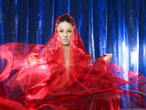 Mujer joven mística en seda roja en fondo azul imágenes de archivo libres de regalías