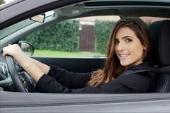 Mujer joven magnífica con el pelo largo que se sienta en cámara de mirada feliz sonriente de la conducción de automóviles foto de archivo