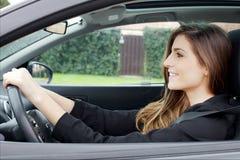 Mujer joven magnífica con el pelo largo que se sienta en la sonrisa de la conducción de automóviles feliz fotografía de archivo libre de regalías