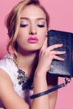 Mujer joven magnífica con el pelo rizado rubio y el maquillaje blando, en ropa elegante con los accesorios Imagen de archivo libre de regalías