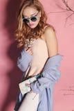 Mujer joven magnífica con el pelo rizado rubio y el maquillaje blando, en ropa elegante con los accesorios Fotografía de archivo libre de regalías