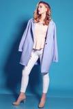 Mujer joven magnífica con el pelo rizado rubio y el maquillaje blando, en ropa elegante con los accesorios Foto de archivo