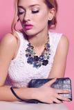 Mujer joven magnífica con el pelo rizado rubio y el maquillaje blando, en ropa elegante con los accesorios Fotos de archivo libres de regalías