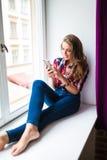 Mujer joven magnífica con el pelo rojo largo que comprueba el correo electrónico y que envía el mensaje del SMS en el teléfono mó Foto de archivo