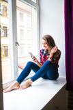 Mujer joven magnífica con el pelo rojo largo que comprueba el correo electrónico y que envía el mensaje del SMS en el teléfono mó Fotografía de archivo libre de regalías
