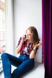 Mujer joven magnífica con el pelo rojo largo que comprueba el correo electrónico y que envía el mensaje del SMS en el teléfono mó Imagen de archivo