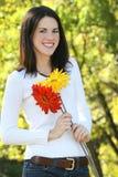 Mujer joven magnífica con las flores en un parque Imagen de archivo libre de regalías