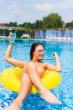 Mujer joven magnífica con las gafas de sol y el tarro con la bebida fría que se sienta en flotador inflable en piscina en día de  fotos de archivo