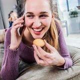 Mujer joven magnífica de risa que habla en el smartphone, comiendo una galleta Imágenes de archivo libres de regalías