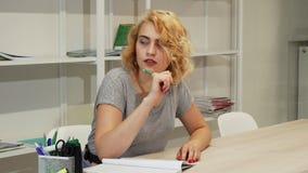 Mujer joven magnífica que hace notas mientras que estudia fotos de archivo