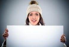 Mujer joven magnífica que lleva a cabo una muestra en blanco fotos de archivo libres de regalías