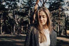 Mujer joven magnífica que presenta en cámara en el fondo de los árboles en parque fotos de archivo