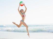 Mujer joven magnífica que salta en la playa que sostiene una pelota de playa Fotos de archivo libres de regalías