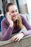 Mujer joven magnífica sonriente que habla en su smartphone, acostándose Fotografía de archivo