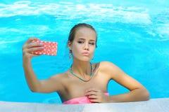 Mujer joven magnífica que toma la foto de sí misma en la piscina Fotos de archivo libres de regalías