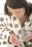 Mujer joven mal mal atractiva que siente enferma tomando la medicina con un vidrio de agua Imagenes de archivo