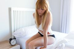 Mujer joven malsana con el dolor de estómago que se inclina en la cama en casa Imagenes de archivo