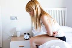 Mujer joven malsana con el dolor de estómago que se inclina en la cama en casa Fotos de archivo libres de regalías