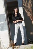 Mujer joven menuda con los talones muy largos del desgaste del pelo y los pantalones blancos Imagenes de archivo