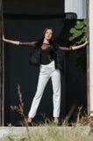 Mujer joven menuda con los talones muy largos del desgaste del pelo y los pantalones blancos Imagen de archivo