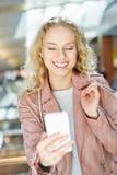 Mujer joven mientras que hace compras lee un mensaje de texto Foto de archivo