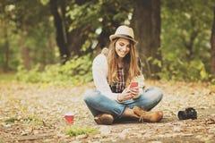 Mujer joven milenaria feliz en parque en otoño usando smartphone Imagen de archivo libre de regalías