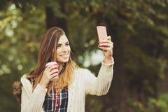 Mujer joven milenaria moderna con el café para llevar que toma un selfie en parque en otoño Imágenes de archivo libres de regalías