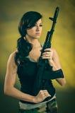 Mujer joven militarizada con el rifle de asalto fotografía de archivo libre de regalías