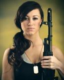 Mujer joven militarizada con el rifle de asalto Foto de archivo libre de regalías