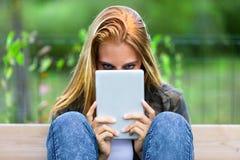 Mujer joven misteriosa que mira sobre una tableta-PC fotografía de archivo