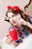 Mujer joven modela atractiva, hermosa que se relaja en cama con la sonrisa feliz del teléfono celular móvil y de la taza roja y q Fotografía de archivo