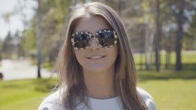 Mujer joven moderna en gafas de sol de la moda con el ornamento del leopardo metrajes