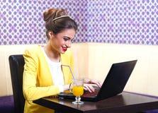 Mujer joven moderna hermosa que se sienta en el ordenador portátil Imagen de archivo libre de regalías