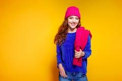 Mujer joven moderna que lleva el suéter azul y sombrero rosado, y presentación de la bufanda, haciendo la expresión facial divert fotografía de archivo