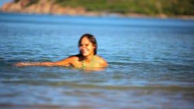Mujer joven morena alegre en la agua de mar almacen de metraje de vídeo