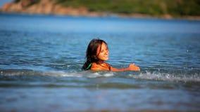 Mujer joven morena alegre en la agua de mar metrajes