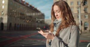 Mujer joven morena atractiva que manda un SMS en el teléfono mientras que se coloca en una calle de la ciudad Imágenes de archivo libres de regalías