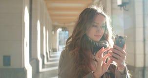 Mujer joven morena atractiva que manda un SMS en el teléfono en una ciudad Fotos de archivo