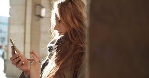 Mujer joven morena atractiva que manda un SMS en el teléfono en una ciudad Imagenes de archivo