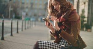 Mujer joven morena atractiva que usa el teléfono en una ciudad metrajes