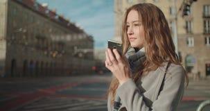 Mujer joven morena atractiva que usa el teléfono en una ciudad almacen de metraje de vídeo