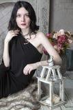 Mujer joven morena en el vestido negro que se sienta cerca de la chimenea Imágenes de archivo libres de regalías
