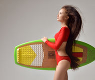 Mujer joven morena hermosa con el pelo y la tabla hawaiana largos Fotografía de archivo