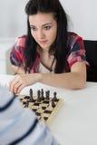Mujer joven morena hermosa del retrato que juega a ajedrez imágenes de archivo libres de regalías