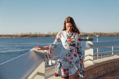 Mujer joven morena hermosa en vestido azul que disfruta de salida del sol por el mar imagen de archivo