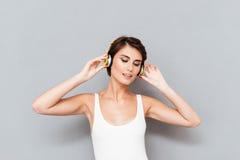 Mujer joven morena hermosa que escucha la música con los auriculares Imágenes de archivo libres de regalías